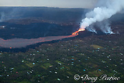 aerial view of lava originating from the east rift zone of Kilauea Volcano, erupting as fountains from fissure 8 in Leilani Estates subdivision, near Pahoa, sending a river of lava through the rural neighborhood toward Kapoho, Puna District, Hawaii ( the Big Island ), Hawaiian Islands, U.S.A.; the Pacific Ocean is visible at the top of the frame.