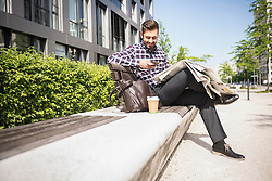 Young man sitting on bench and text messaging on smartphone, Munich, Bavaria, Germany