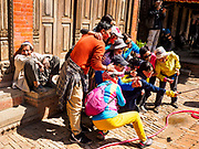 12 MARCH 2017 - BHAKTAPUR, NEPAL:  A Nepali man watches Chinese tourists do selfies during the Holi celebration in Bhaktapur. Holi, a Hindu religious festival, has become popular with non-Hindus in many parts of South Asia, as well as people of other communities outside Asia. The festival signifies the victory of good over evil, the arrival of spring, end of winter, and for many a festive day to meet others. Holi celebrations in Nepal are not as wild as they are in India.    PHOTO BY JACK KURTZ