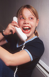 Teenage girl talking on the phone looking excited,