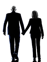one caucasian couple senior walking rear view silhouette  in silhouette studio isolated on white background