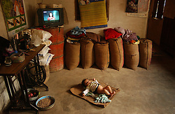 """A baby sleeps inside the house of Mr. Amar Singh Verma, who is the """"sanchuluk"""" or computer operator in the agricultural village of Siradi, about 65 kilometers from Bhopal, India March 1, 2005. The company ITC has installed solar power and computers in the villages so farmers can trade their crops online and shopping malls next to the agricultural markets where they bring their harvest. Already their lifestyles are improving as they are able to communicate with the outside world, have electricity and most importantly wait for good prices to sell their crops. Ami Vitale"""