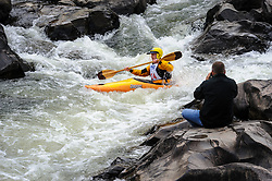 An unidentified spectator  photographs B. J. Browning of St. Charles, Missouri as Browning races in the K1 men's senior plastic class during the slalom course of the 42nd Annual Missouri Whitewater Championships. Browning placed third place in the class. The Missouri Whitewater Championships, held on the St. Francis River at the Millstream Gardens Conservation Area, is the oldest regional slalom race in the United States.