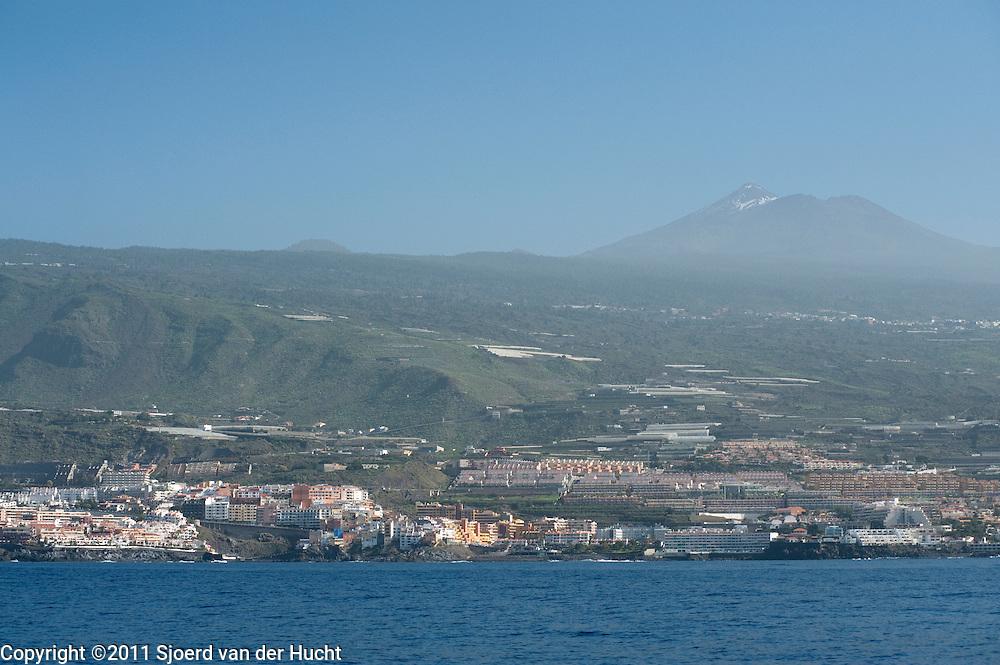 Uitzicht vanuit boot op de plaats Los Gigantes, Tenerife. Op de achtergrond de vulkaan El Teide, of Pico del Teide, de op derde na grootste vulkaan van de wereld en is het de hoogste berg van Spanje - View from boat at the town Los Gigantes, Tenerife, Spain. On the background the Mount Teide, the third largest volcano in the world from its base and it is the highest elevation in Spain