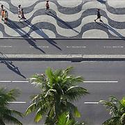 Walkers exercise along the beachfront of Copacabana beach, Rio de Janeiro,  Brazil. 19th July 2010. Photo Tim Clayton..