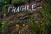 The word FRAGILE painted onto the hillside as an artwork to focus walkers on caring for the enviroment, 4th April 2016, Lagrasse, France.