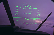 We look through the windscreen of a Royal Air Force C-130-J Hercules to see a pilots-eye view of his fixed head-up-display (HUD), while in flight over Hampshire during the Farnborough Air Show. We see the aircraft flying data in green set against the magenta colour (color) of the clouds and sky beyond. The pilot will see the statistics that are important aspects of his aeroplane's altitude, compass heading, localiser, air speed, pitch, roll and yaw. Head-up displays are increasingly important to military and commercial aircraft (airplanes) when information can be displayed without obstructing the user's front view front. The second type of HUD is mounted within a protective helmet visor. The C-130 Hercules primarily performs the tactical portion of airlift operations. The aircraft is capable of operating from rough, dirt strips and is the prime transport for air dropping troops and equipment into hostile areas. The C-130-J is the newer generation digital version with fully integrated digital avionics; color multifunctional liquid crystal displays including the HUD; state-of-the-art navigation systems with dual inertial navigation system and global positioning system; fully integrated defensive systems; low-power color radar; digital moving map display; new turboprop engines with six-bladed, all-composite propellers; digital auto pilot; improved fuel, environmental and ice-protection systems; and an enhanced cargo-handling system.