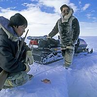 BAFFIN ISLAND,  Nunavut, Canada, Inuit hunters Laimake Palluq & Jayko Apak study fish beside a seal breathing hole on frozen Baffin Bay.