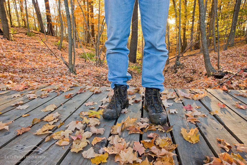 A man hikes over a footbridge near the Presumpscot River in Portland, Maine. Fall.