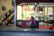 A women cleans outside a shop early in the  morning before rush hour.