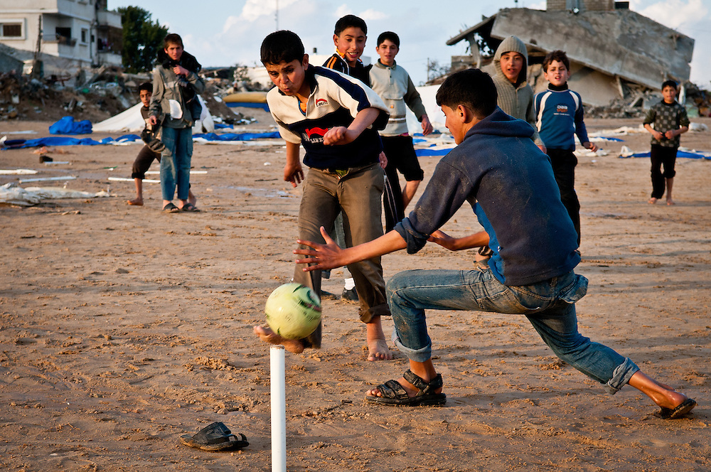 Children play soccer amid the wreckage of homes in Jabaliya after a series of late winter rain storms.