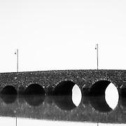 A stone bridge in a thick fog in Ireland.