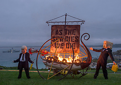 """© Licensed to London News Pictures; 11/06/2021; St Ives, Cornwall UK. G7 summit in Cornwall. Extinction Rebellion stage a protest on the Island above St Ives as they set fire to a model Viking ship with a sail saying """"As the Sea Dies We Die"""" on the first day of the G7 summit. The scene has performers dressed as UK Prime Minister Boris Johnson being controlled by a man representing the Big Oil fossil fuel companies setting fire to the boat and throwing wads of money. Photo credit: Simon Chapman/LNP."""