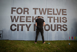 """© Licensed to London News Pictures . 05/06/2015 . Manchester , UK . A man urinates against a poster reading """" For twelve weeks this city is ours """" . Evening concerts featuring headliners , The Courteeners , playing a homecoming gig , at Heaton Park in Manchester in front of 25,000 people , the evening before the Parklife music festival . Photo credit : Joel Goodman/LNP"""