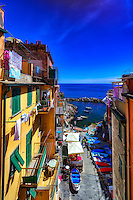 """""""A day in the life of Riomaggiore""""…<br /> <br /> I began my daily journey at the northern most town of Monterosso and took the train to the southernmost town of Riomaggiore. Upon arriving in this picturesque seaside village and moving down to the water's edge, I noticed proprietor Francesco in front of a tiny boat rental sign.  After arranging an evening sail up the coast, I was able to focus on the colorful persona of Riomaggiore. That evening I sailed up the coast photographing each Cinque Terre town along the way aboard the Angelina Dada. Upon arriving back home in Monterosso, soft light illuminated the sky and azure sea of the Mediterranean convincing me to sail all the way back to Riomaggiore with my gracious guides Claudio and Eddie of """"Cinque Terre dal Mare"""" sailing excursions. We arrived just in time for a perfect sunset. After a nice dinner...I caught the last train at midnight back home to Monterosso. A very long day, but worth every minute!"""