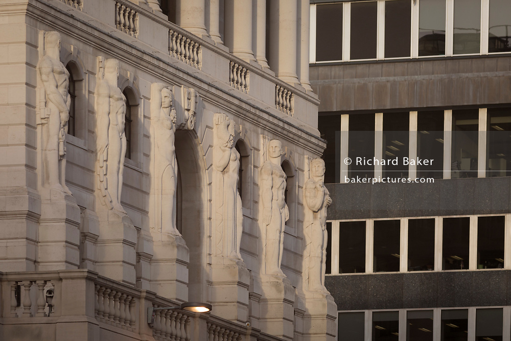 """The Telamon Portland stone figures of the Bank of England on Threadneedle Street in the heart of the Square Mile, the capital's historical and financial centre, on 1st November 2017, in the City of London, England. The Bank of England, is the central bank of the United Kingdom and the model on which most modern central banks have been based. Established in 1694, it is the second oldest central bank in the world. Sir Herbert Baker's rebuilding of the Bank, demolishing most of Sir John Soane's earlier building, was described by architectural historian Nikolaus Pevsner as """"the greatest architectural crime, in the City of London, of the twentieth century""""."""