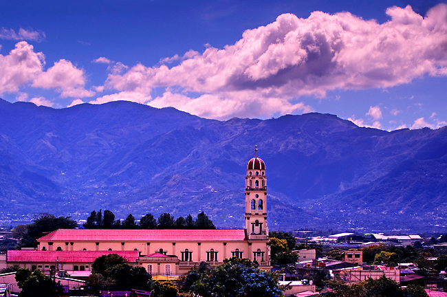 The Red Dome Of The Cathedral Of Alajuela Rises Above The Town Of Alajuela, Costa Rica.  The Central Volcanic Cordillera Mountain Range Rises Behind The Church.