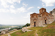 The Hagia Triada Church. View over the valley. A woman standing on a wall taking a photograph. Berat upper citadel old walled city. Albania, Balkan, Europe.