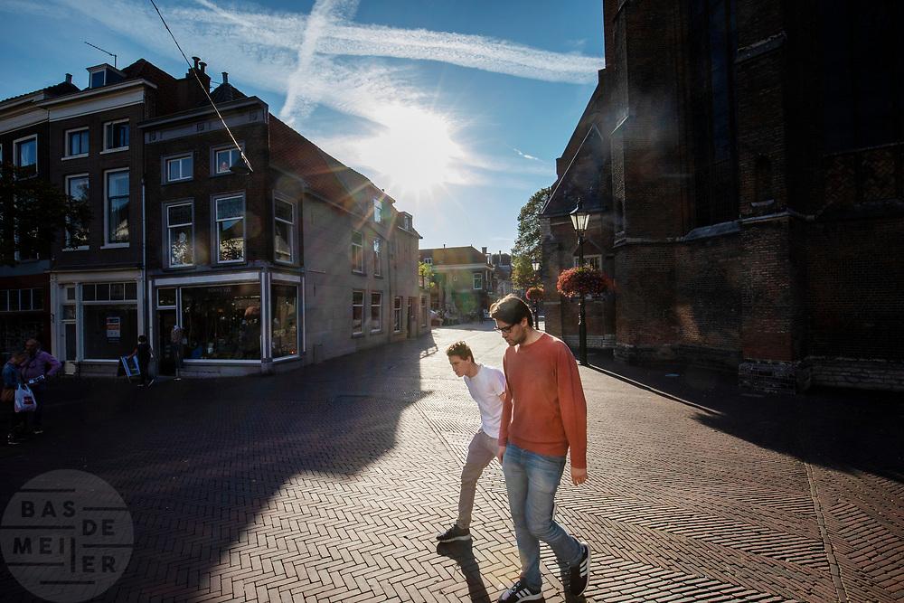 Twee mannen lopen door de binnenstad van Delft.<br /> <br /> Two men walk in the city center of Delft.