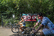 People cycle beside a sign which suggests that swimming, BBQ-ing and littering is forbidden as well as urging people to keep the social distance near River Lea in east London on Friday, Aug 7, 2020.<br /> The UK has seen its hottest day in August for 17 years, as temperatures reached more than 36C (96.8F) in south-east England, British press reports. Crowds of people headed to the coasts and rivers to enjoy the weather, but people have been urged to adhere to social distancing. (VXP Photo/ Vudi Xhymshiti)