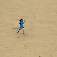 Europe, Ireland, Brittas Bay. Girl running down dune at Brittas Bay.