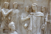 Trajan and Dacia, Arch of Trajan at Beneventum, AD 114. Trajan raises up the conquered province, Dacia. Behind columnists cross Trajan's famous Danube bridge into the new province.  Two local river gods in the lower corners frame the scene.