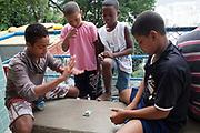 Young boys playing top trumps football cards on a concrete bench, favela Santa Marta in Botafogo, Rio de Janeiro.