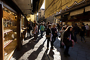 "Shoppers browse the many jewellers shop displays on Florence's Ponte Vecchio. The Ponte Vecchio (""Old Bridge"") is a Medieval bridge over the Arno River, in Florence, Italy, noted for still having shops built along it, as was once common. Butchers initially occupied the shops; the present tenants are jewellers, art dealers and souvenir sellers. It has been described as Europe's oldest wholly-stone, closed-spandrel segmental arch bridge. To enforce the prestige of the bridge, in 1593 the Medici Grand Dukes prohibited butchers from selling there; their place was immediately taken by several gold merchants."