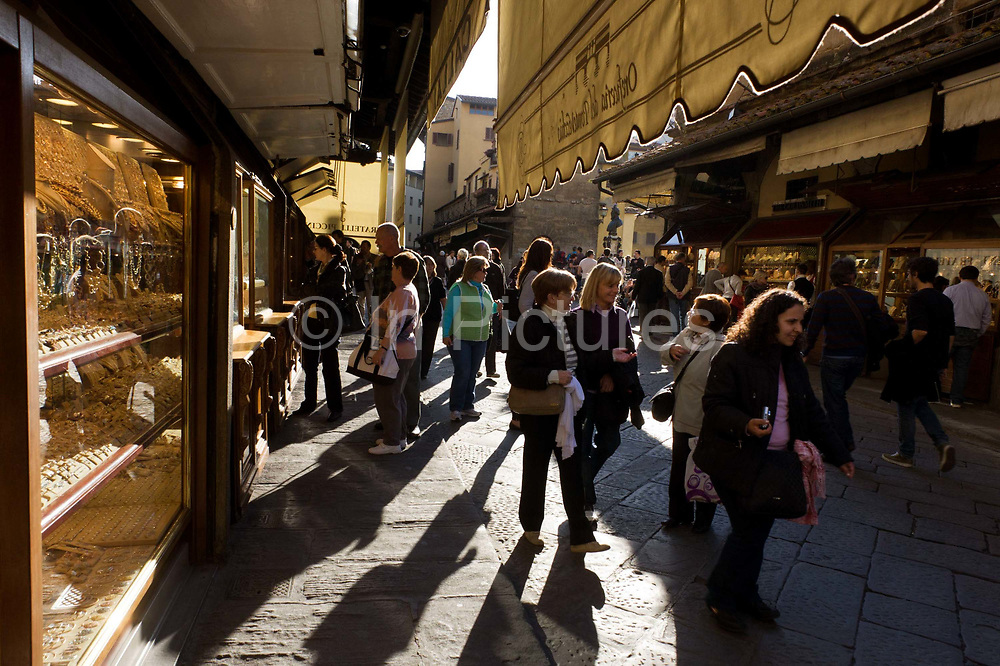 """Shoppers browse the many jewellers shop displays on Florence's Ponte Vecchio. The Ponte Vecchio (""""Old Bridge"""") is a Medieval bridge over the Arno River, in Florence, Italy, noted for still having shops built along it, as was once common. Butchers initially occupied the shops; the present tenants are jewellers, art dealers and souvenir sellers. It has been described as Europe's oldest wholly-stone, closed-spandrel segmental arch bridge. To enforce the prestige of the bridge, in 1593 the Medici Grand Dukes prohibited butchers from selling there; their place was immediately taken by several gold merchants."""