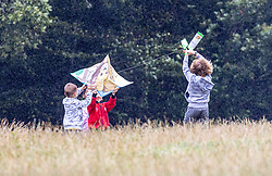 Licensed to London News Pictures. 30/07/2021.Dorking, UK. Kids enjoy a bit of kite flying on top of Box Hill in Surrey despite the unseasonal stormy conditions today. Storm Evert hit the South Coast of England this morning with winds speed in excess of 65mph as the Met Office issue weather warnings for high winds, coastal gales and heavy rain with disruption to travel. Photo credit: Alex Lentati/LNP