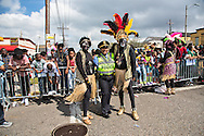 Memebers of the The Krewe of Zulu pose with a police officer on Mardi Gras day in New Orleans.