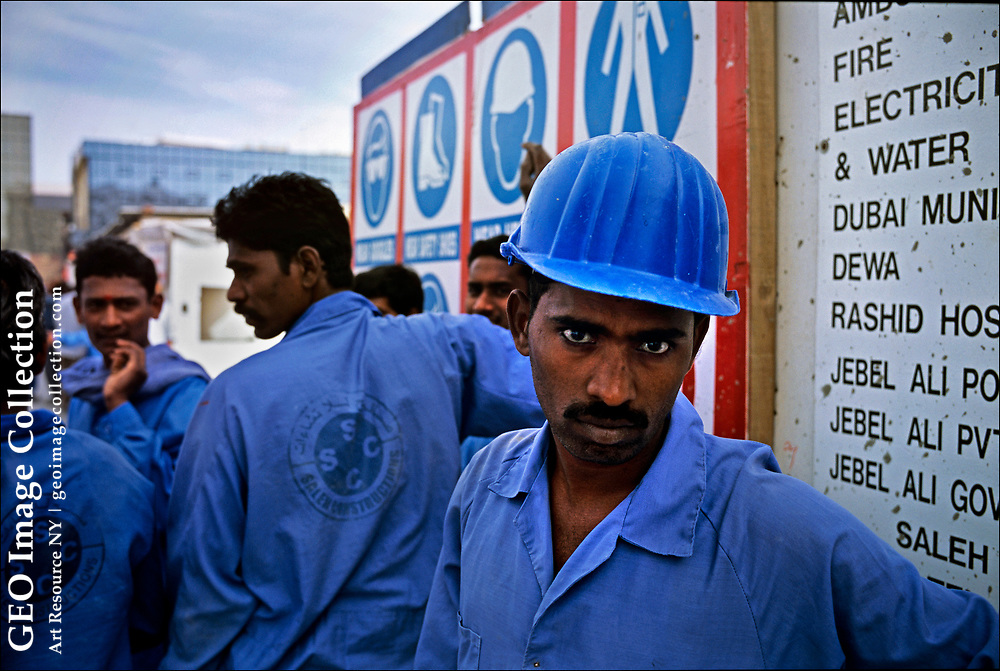 South Asian workers at a construction site in Dubai await busses that will take them to desert labor camps, enclaves for foreign workers that resemble barracks for a Third World army.  Stripped of their passports and preyed upon by foreign recruitment agencies that charge thousands of dollars for employment visas, workers earn between $200 and $400 a month  about the same as the cost of staying a single night in one of Dubai's luxury hotels that these workers helped build.