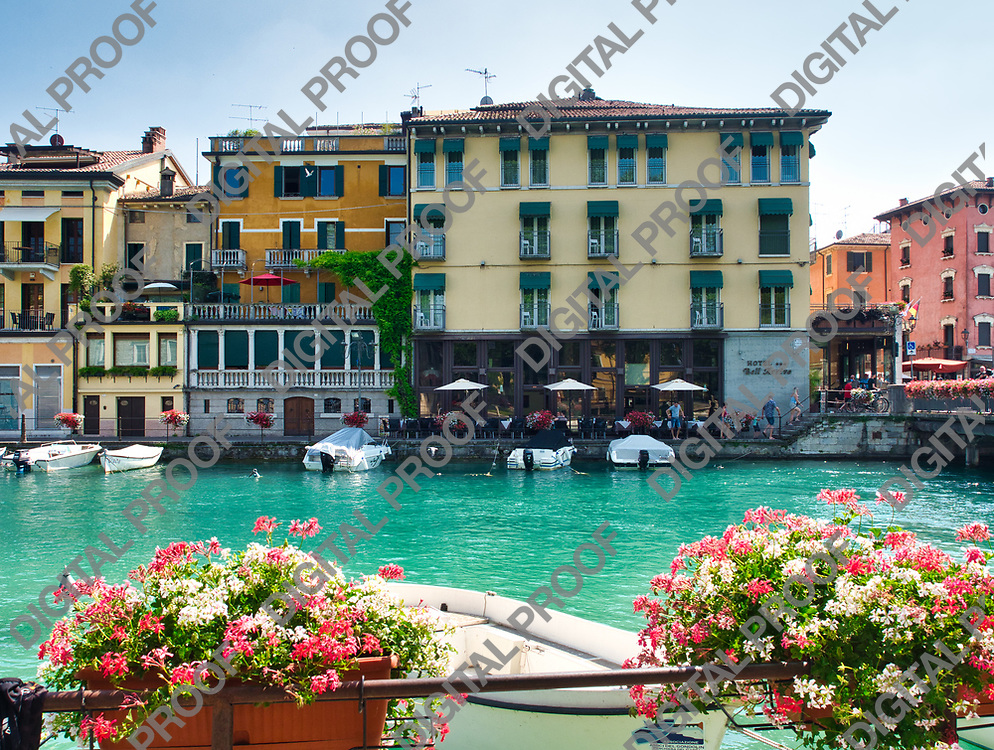 View of the Peschiera del garda canal in Lake Garda, Italy with parked speedboats and buildings with local businesses with few people during a summer afternoon