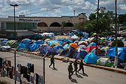"""Mexican National Guard members patrol next to a makeshift encampment occupied by asylum seekers, most of whom were sent back to Mexico from the U.S. under the """"Remain in Mexico"""" program officially named Migrant Protection Protocols (MPP), by the Gateway International Bridge in Matamoros, Tamaulipas, Mexico, October 6, 2019."""