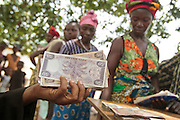 A staff from a local bank holds a handfull of money during a UNICEF-sponsored social cash transfer programme distribution in the village of Julijuah, Bomi county, Liberia on Tuesday April 3, 2012. Beneficiary households receive monthly transfers that vary according to the size of the household, with additional sums provided for each child enrolled in school. Families are selected for participation in the programme based on two key criteria: they must be both extremely poor and labour-constrained.