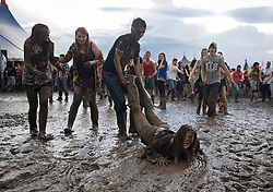 © Licensed to London News Pictures. 26/08/2011. Reading, UK. Katherine Vincent (18) being dragged through mud on day one of Reading Festival 2011 in Reading, Berkshire today (26/08/2011). Photo credit: Ben Cawthra/LNP