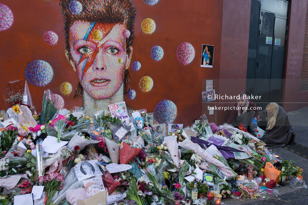 Fans of iconic English music artist David Bowie who died from Cancer at the age of 69 on Sunday 10th January, gather to pay their respects at a makeshift shrine of flowers and tributes to the local boy from Brixton, south London. Commuters stopped-by before entering the nearby underground station to take pictures and silently remember their hero's great days playing the soundtracks of their childhoods.