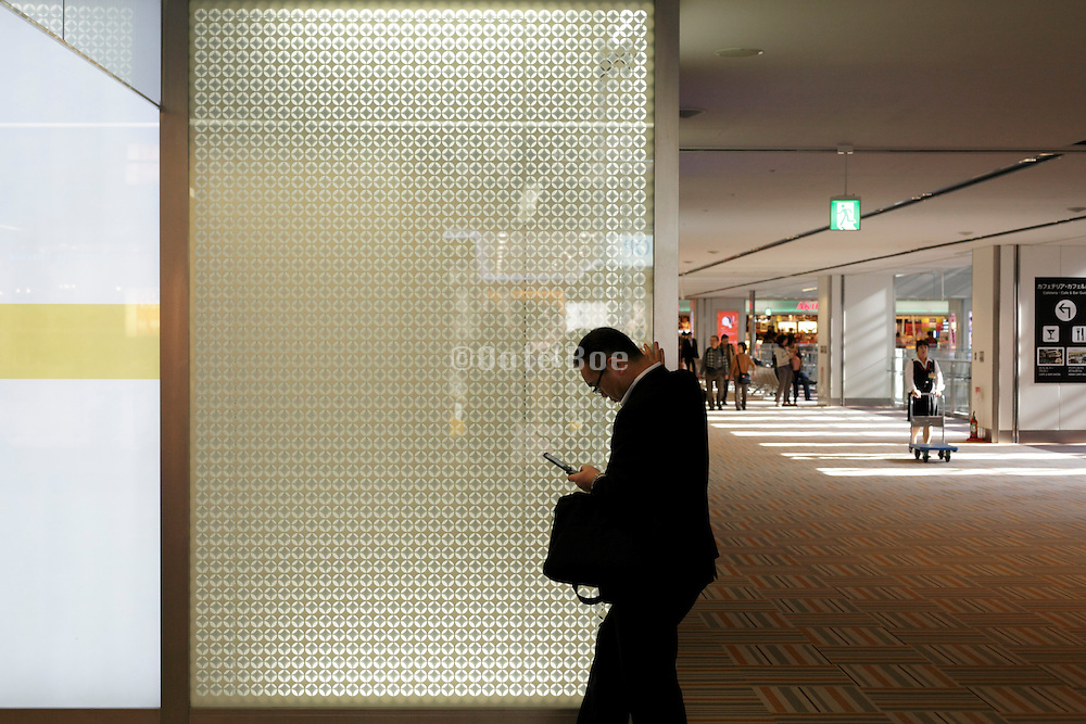 businessman in airport lobby checking his messages on a mobile phone