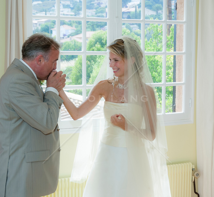 father of the bride kissing his daughter's hand before the wedding