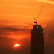 Makati high rise construction silhouette as the sun sets behind clouds over Manila Bay