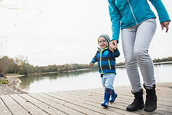 Mother and son walking hand in hand on a landing stage over lake in autumn