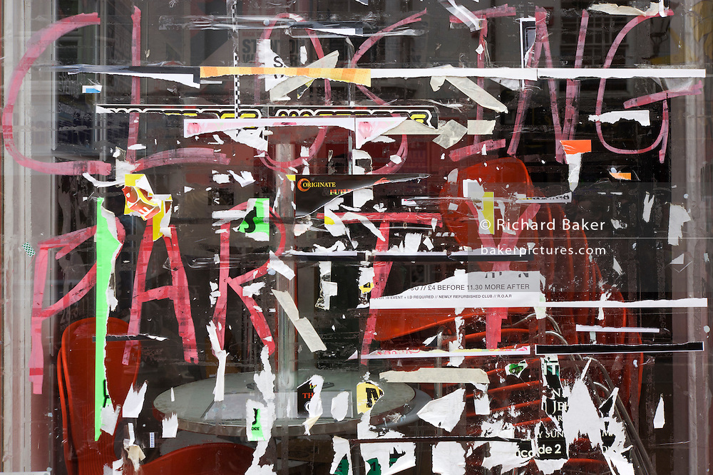 The words Closing Party are almost covered by fly-posters on a closed shop window, the victim of the economic recession.