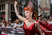 New York, NY - 30 June 2019. The New York City Heritage of Pride March filled Fifth Avenue for hours with participants from the LGBTQ community and it's supporters. A participant wearing  a red dress and a tiara waves to the crowd.