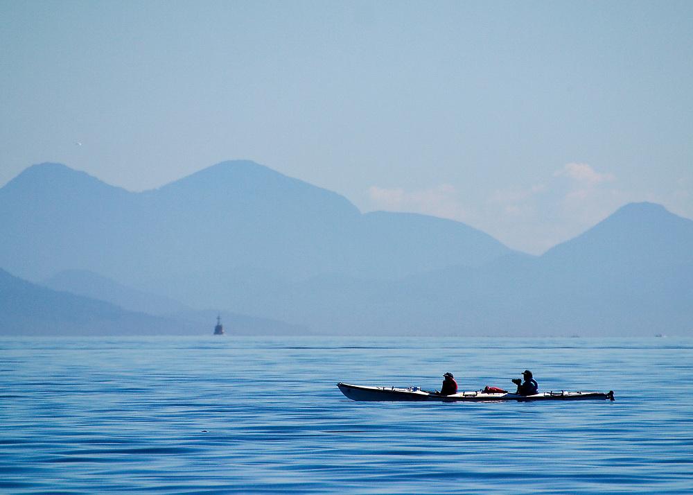 Alaska. SE. Inside Passage. A tandem sea kayak cruises the waters of the Inside Passage.