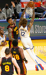 Mar 26, 2021; San Francisco, California, USA; Golden State Warriors forward Kelly Oubre Jr. (12) dunks over Atlanta Hawks forward John Collins (20) during the fourth quarter of an NBA basketball game at Chase Center. Mandatory Credit: D. Ross Cameron-USA TODAY Sports