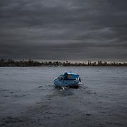 Locals cross the Dnieper river by boat in Kherson, a region bordering Crimea.