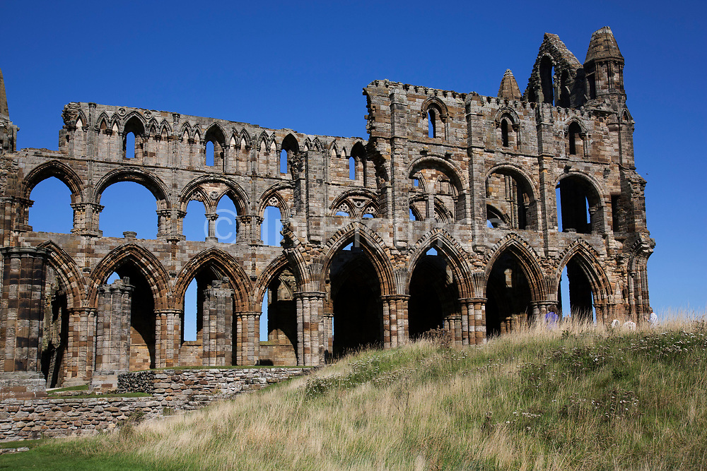 Whitby Abbey is a ruined Benedictine abbey on the East Cliff above Whitby. It was disestablished during the Dissolution of the Monasteries under the auspices of Henry VIII, and was famously the inspiration for Bram Stoker's gothic tale of 'Dracula'. Whitby is a seaside town, port in the county of North Yorkshire, originally the North Riding. Situated on the east coast at the mouth of the River Esk. Tourism started in Whitby during the Georgian period and developed. Its attraction as a tourist destination is enhanced by its proximity to the high ground of the North York Moors, its famous abbey, and by its association with the horror novel Dracula. Yorkshire, England, UK.