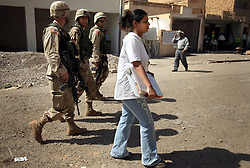 Alyaa Abdul Hassan Abbood, 23, a translator, walks with soldiers to the local courthouse where they will give Iraqi civilians monetary compensation for damages caused by U.S. troops in Baghdad, Iraq, Sept. 27, 2003.