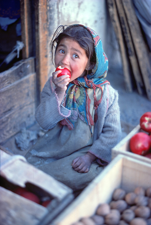A young girl eats a red apple in the market in Leh, the capital of Ladakh, India.