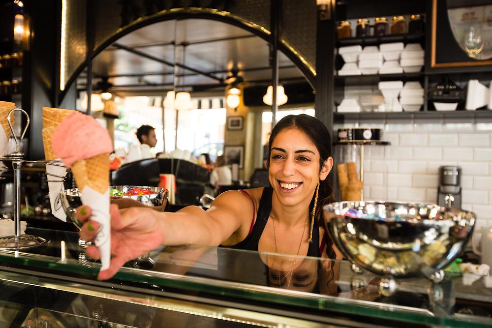Shelly Azizyan serves ice cream to customers of Anita Ice Cream shop, in Tel Aviv's Neve Tzedek neighborhood